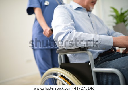 Nurse pushing an injured patient on a wheelchair - stock photo