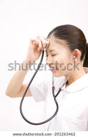 Nurse putting a stethoscope to forehead
