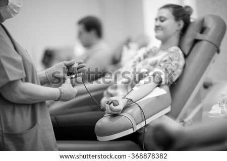 Nurse receiving blood donation in hospital - stock photo