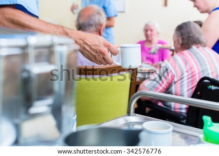 Nurse serving food in nursing home - stock photo