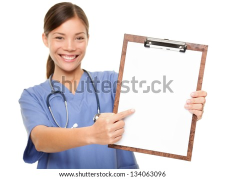 Nurse showing medical sign clipboard copy space. Female medical doctor or nurse pointing at blank empty copyspace. Young mixed race Asian Caucasian woman model in blue scrubs isolated on white. - stock photo