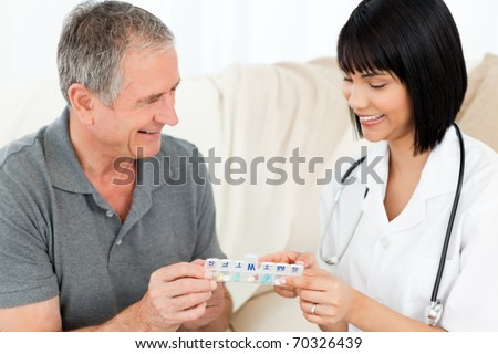 Nurse showing pills to her patient - stock photo
