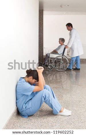 Nurse sitting on the ground in the hallway getting depressed - stock photo