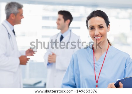 Nurse smiling at camera while doctors are talking together in medical office - stock photo
