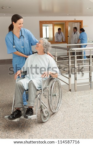 Nurse smiling at old women sitting in wheelchair in hospital corridor - stock photo