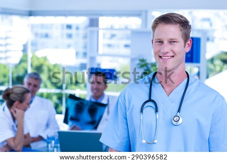 Nurse smiling at the camera during a meeting - stock photo