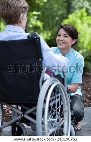 Nurse smiling to elderly woman on wheelchair in garden - stock photo