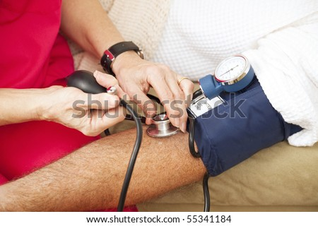Nurse taking a patient's blood pressure using a sphygmomanometer.  Closeup view. - stock photo