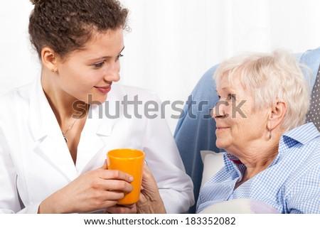 Nurse taking care of elderly woman, horizontal - stock photo