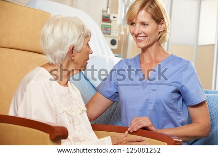 Nurse Taking To Senior Female Patient Seated In Chair By Hospital Bed - stock photo