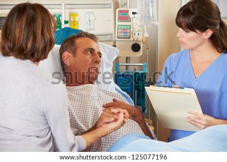 Nurse Talking To Couple On Ward - stock photo