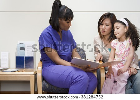 Nurse talking to mother and daughter - stock photo