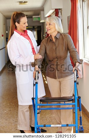 Nurse talking to senior patient with walker in hospital