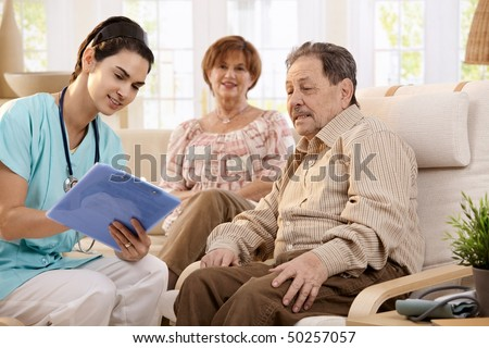Nurse talking with elderly people and making notes during examination at home, smiling. - stock photo