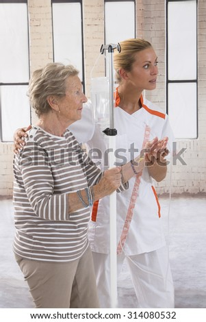 Nurse walking next to a patient with IV drip