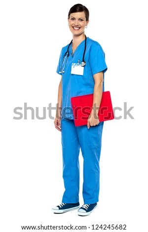 Nurse wearing blue uniform and holding red clipboard. Full length studio shot. - stock photo