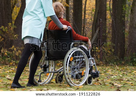 Nurse with disabled lady on wheelchair outdoors - stock photo