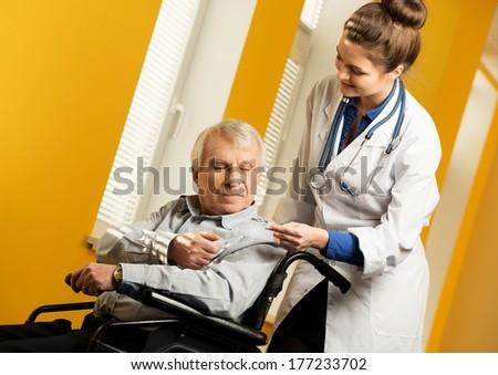 Nurse woman giving client's card to senior man in wheelchair  - stock photo