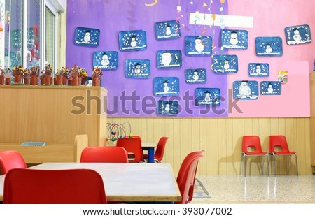 Nursery class with small red chairs and children's drawings on the walls - stock photo