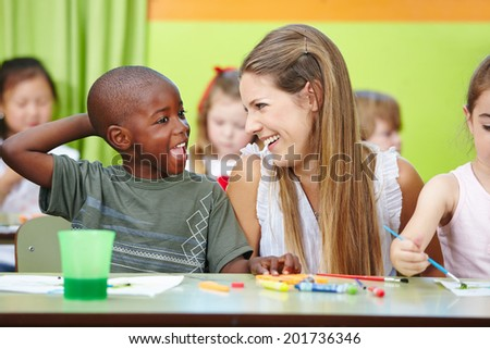 Nursery teacher and children having fun together in a kindergarten group - stock photo