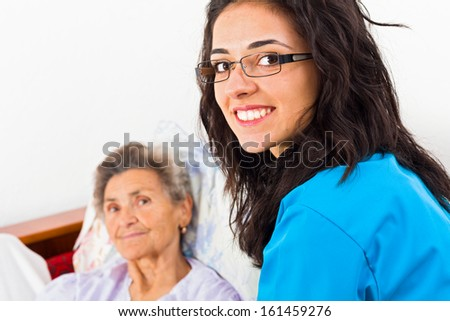 Nurses caring for elderly patients suffering from disease in nursing home.  - stock photo