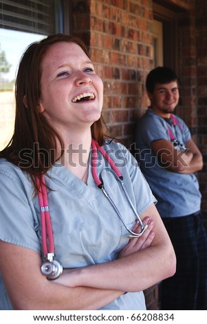 Nurses laughing man and woman having fun - stock photo
