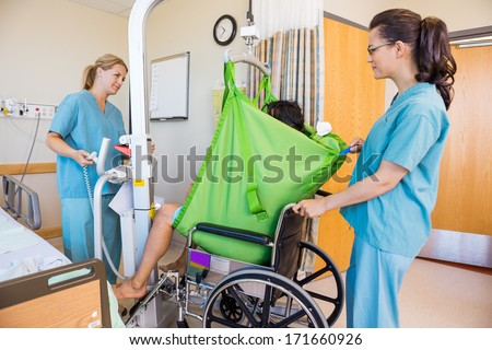 Nurses transferring male patient from hydraulic lift to wheelchair in hospital - stock photo