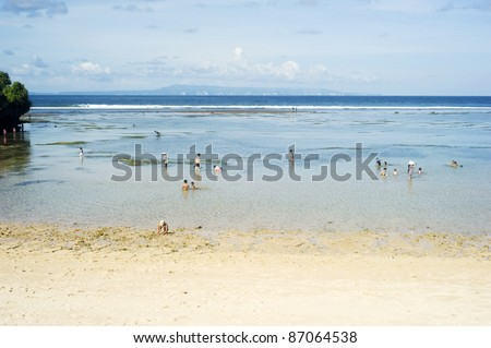 NUSA DUA,BALI, INDONESIA - APRIL 17: People swim in the ocean during tide ebb on April 17, 2011 in Nusa Dua,  Indonesia. Nusa Dua is known as enclave of large international 5-star resorts in Bali. - stock photo