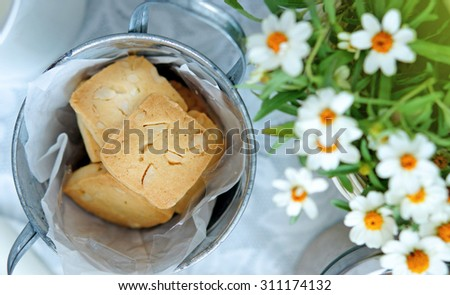 Nut cookies in small bucket, decorated with tiny white flowers - stock photo