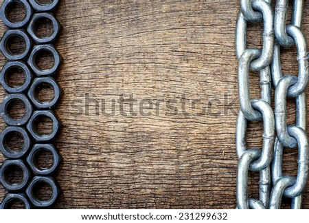 nut on the left side and the right side of the iron chain in an old cracked wooden background - stock photo