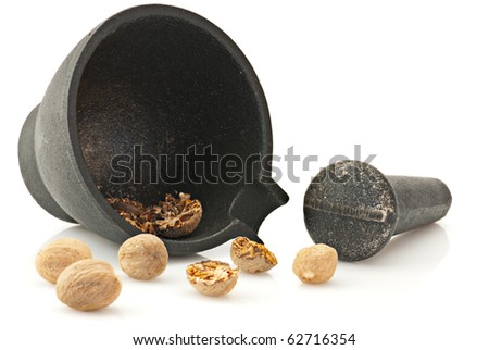 Nutmeg and kitchen utensil: mortar with pestle isolated on white - stock photo