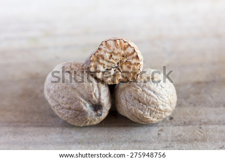 Nutmeg on an old wooden table - stock photo