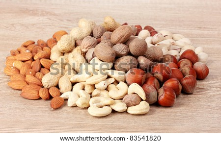 nutmeg, peanuts, hazelnuts and almonds on wooden background