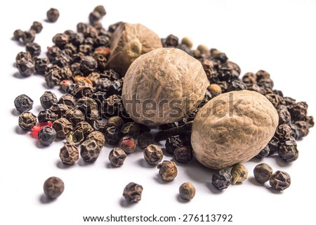 Nutmegs and black pepper on white background - stock photo