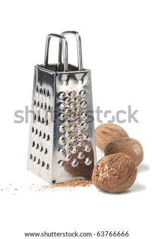 Nutmegs and grater isolated on white background. Shallow dof - stock photo