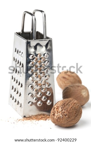 Nutmegs and grater on white background. Shallow dof - stock photo