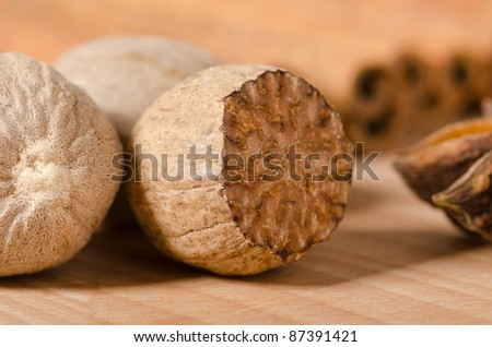 Nutmegs and star anise with cinnamon sticks in the background - stock photo