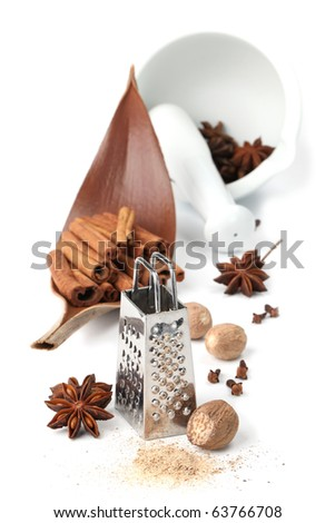 Nutmegs, cloves, anise and cinnamon with grater and mortar isolated on white background. Shallow dof - stock photo