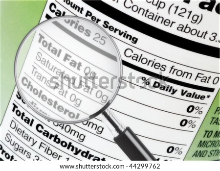 Nutrition information under a magnifying glass - stock photo