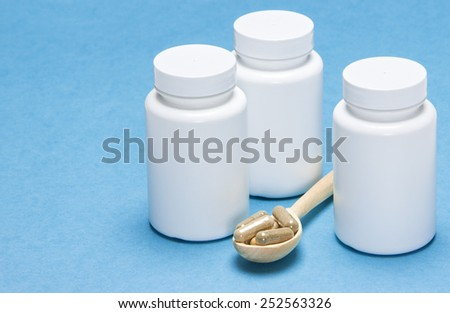 Nutritional supplements: capsules in a wooden spoon with white jars on a blue background - stock photo