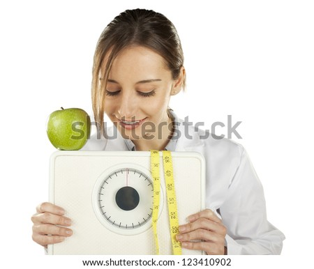 Nutritionist watching and holding a weight scale and green apple. Healthy eating and lifestyle concept - stock photo