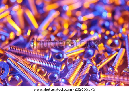 Nuts and bolts background in bright colorful lights - stock photo