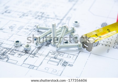 Nuts and bolts close-up over  architectural plan
