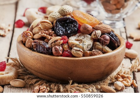 Nuts and dried fruit mix, healthy and wholesome food. Vintage wooden background, selective focus