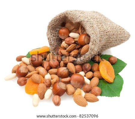 nuts  and dried fruits in a linen basket on green leaves isolated on white background - stock photo