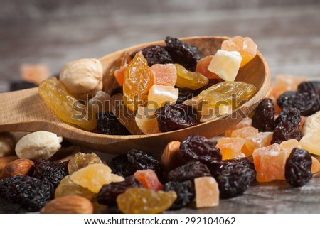 Nuts and dried fruits mix on a rustic sack and wooden background - stock photo