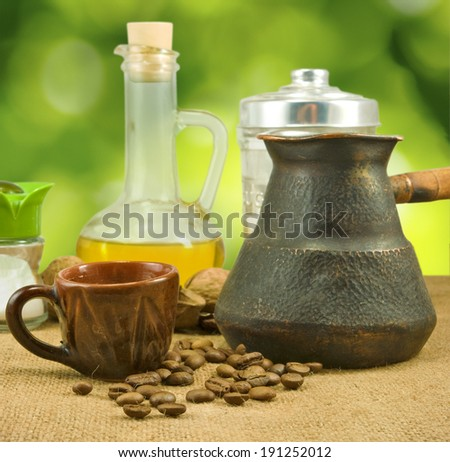 nuts, butter, salt shaker, coffee beans, a cup on a green background closeup - stock photo