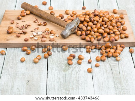 Nuts. Hazelnuts and hammer on shabby wooden table - stock photo