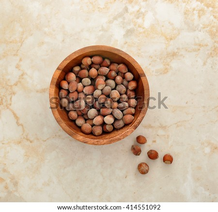 nuts hazelnuts in a wooden bowl on a marble background. top view - stock photo