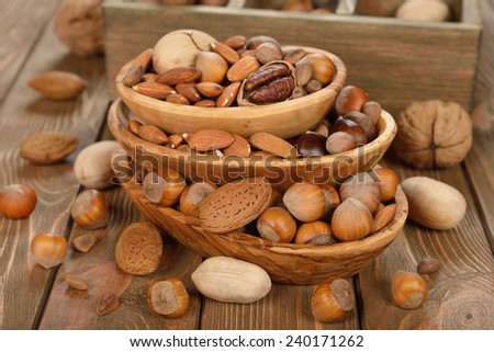 Nuts in a bowl on a brown background - stock photo